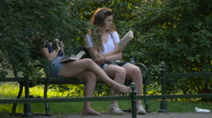 Two girls sitting on a bench in Krakow Stock Footage