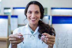 Stock Photo of Blurry picture of a female optician showing glasses
