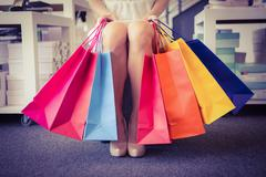 Woman trying on court shoes with many shopping bags - stock photo