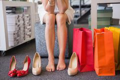 Woman trying on many shoes - stock photo