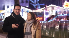 Happy romantic couple pose to take a selfie at Christmas fair - stock footage