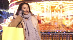 Portrait of beautiful smiling woman talking on mobile phone at Christmas fair - stock footage