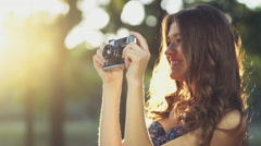Young female takes pictures with an old camera slow motion Stock Footage