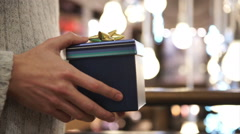 Close up on hands of man giving a Christmas gift to his loved one.  Stock Footage