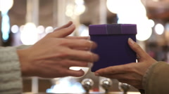 Close up on hands of woman giving a Christmas gift to her loved one - stock footage