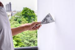 Wall refurbishment with plastering using putty knife. - stock photo