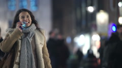 Young woman walking through city at night and talking on mobile phone. - stock footage