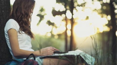 Young female with a map and compass in forest slow motion Stock Footage
