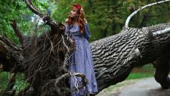 Girl with a wreath stands near the roots of a fallen tree. Stock Footage