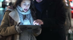 Couple using computer tablet outdoors in the city at Christmas time - stock footage