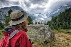 Woman hiker looks high mountain - stock photo
