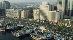 Aerial Dhows anchored Dubai Creek Waterfront city buildings UAE Stock Footage