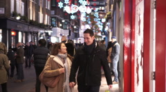 Attractive romantic couple shopping in the city at Christmas time - stock footage