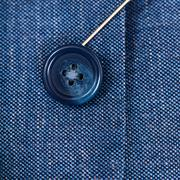 attaching of button to blue silk cloth by needle - stock photo
