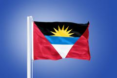 Flag of Antigua and Barbuda flying against a blue sky Stock Photos