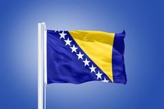 Flag of Bosnia and Herzegovina flying against a blue sky Stock Photos
