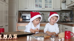 Two kids preparing christmas cookies and put them on baking tray together Stock Footage