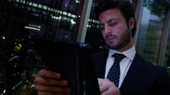 male Western European business technology tablet finance banking night hotel - stock footage