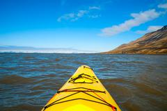 Kayaking on the sea in Svalbard, first person view - stock photo
