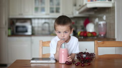 Happy school boy drinking healthy smoothie as a snack at home, eating cherries Stock Footage