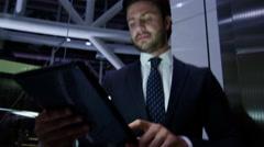 Male Western European business technology tablet finance night hotel lift Stock Footage