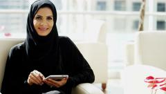 Emirati business female portrait abaya Dubai insurance growth tablet technology - stock footage