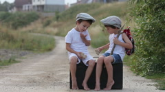 Two boys, sitting on a big old vintage suitcase, playing with toys Stock Footage