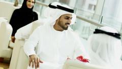 male female Emirati clothing hotel atrium coffee relaxation travel tourism - stock footage