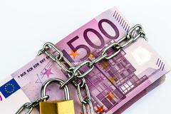 euro notes with chain and padlock - stock photo