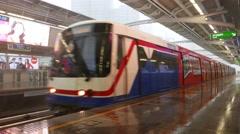 Modern overground metro train arrive to empty platform, doors opens, heavy rain Stock Footage