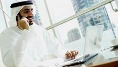 Arabic male stock shares commodity assets laptop computer smart phone technology Stock Footage