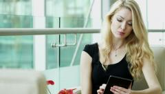 blonde female Western Caucasian business finance traveller technology tablet - stock footage