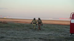 Two rescuer fireman going across the field. Stock Footage
