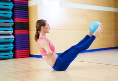 Pilates woman stability ball teaser exercise - stock photo