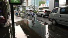 Asian woman cross puddle on sidewalk, walk on small stones in water Stock Footage