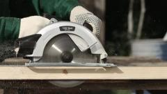 Worker in gloves cutting a wooden plank with hand circular saw Stock Footage
