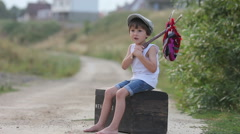 Cute little boy, sitting on a big old suitcase, vintage Stock Footage