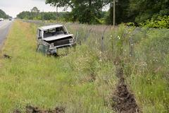 Accident - Car in a ditch on the grass - stock photo