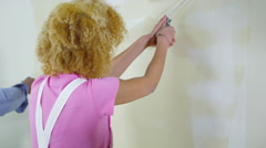4K Happy attractive ethnic couple painting a wall in new home - stock footage