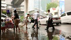 Woman push vendor cart over puddle on roadside, people jump over water Stock Footage