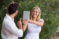 young women taking photos with digital tablet of her boyfriend - stock photo