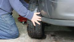 Removing a tire from a car Stock Footage