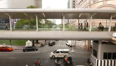 Modern pedestrian overpass over lively road junction, few people walking through Stock Footage