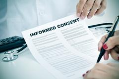 young woman signing an informed consent - stock photo
