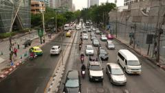 Perspective view on busy city road, vehicles drive towards and pass under Stock Footage