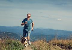 Man running with his dog on the mountain tableland. Stock Photos