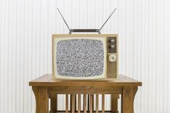 Old Television with Antenna on Wood Table with Static Screen - stock photo