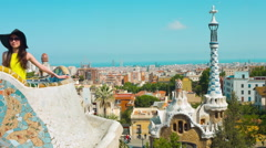 Entrance to Park Guell and girl on main tarrace, Barcelona cityscape 4k Stock Footage