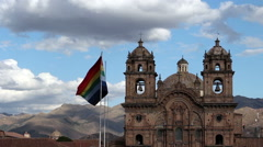 Stock Video Footage of Cusco Flag Flying In Plaza With Church In Background