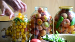 Woman lays tomatoes and cucumbers in jars. Home canning for  winter Stock Footage